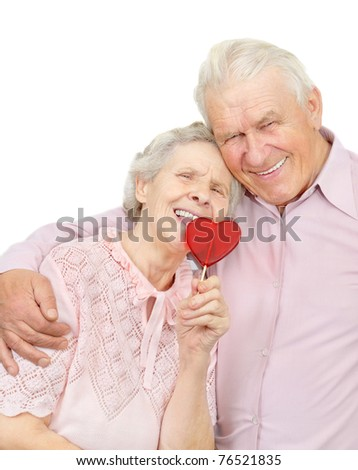 smiling old couple with red heart-shaped candy on white background - stock photo