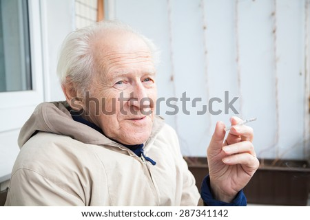 smiling old man enjoying a cigarette on his balcony - stock photo