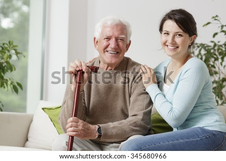 Smiling old man holding a cane and smiling young woman - stock photo