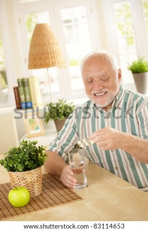 Smiling old man taking medication with water, holding bubble package, sitting at home.? - stock photo