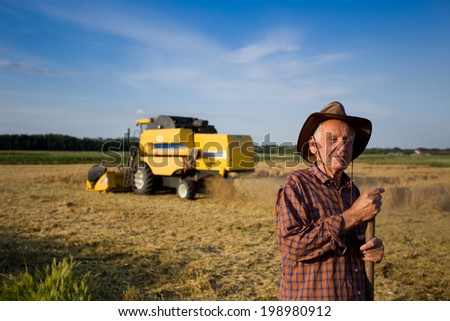 Smiling old peasant standing on field with combine in background - stock photo