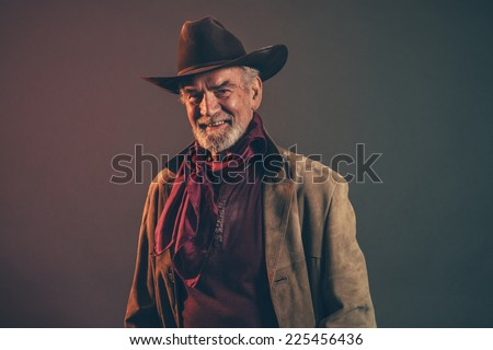 Smiling old rough western cowboy with gray beard and brown hat. Low key studio shot. - stock photo