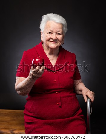 Smiling old woman holding red apple on a dark background - stock photo