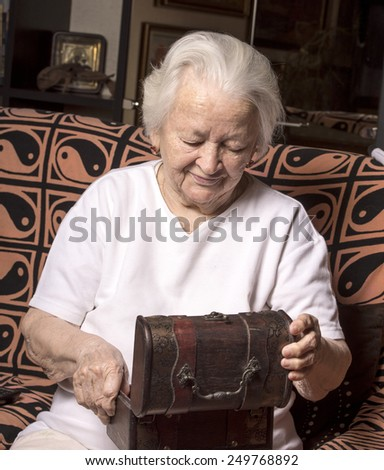 Smiling old woman with casket at home - stock photo