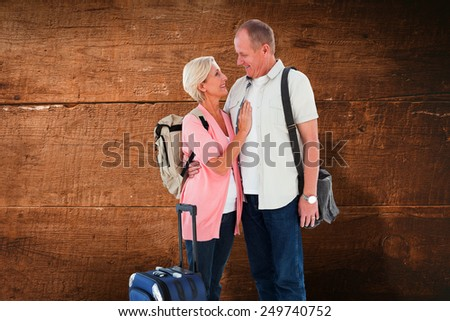 Smiling older couple going on their holidays against overhead of wooden planks - stock photo