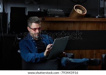 Smiling older man with gray hair in casual jeans sitting in dark room using tablet, working