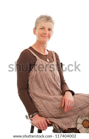 Smiling older woman sits sideways on chair. She wears flowered boots and brown cotton shift dress. Closeup, isolated on white background, vertical, copy space.
