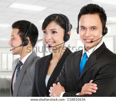 Smiling operator doing her job with a headset in the office