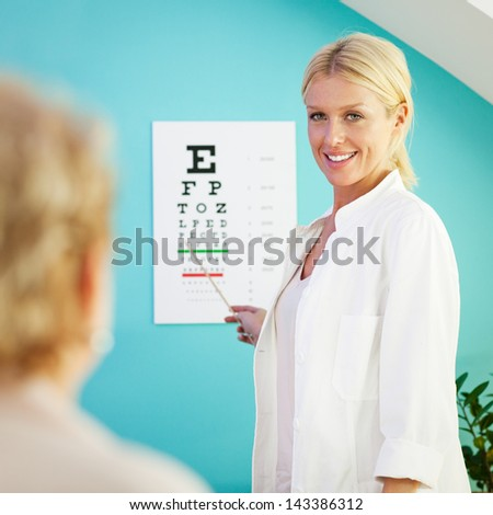 Smiling optician pointing at the letters on the eye chart for her patient to read. - stock photo