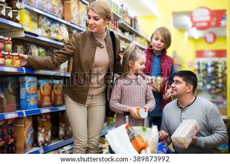Smiling ordinary family with children buying groceries in supermarket - stock photo