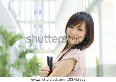 Smiling outdoor young executive with diary - stock photo