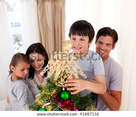 Smiling parents and children decorating a Christmas tree at home