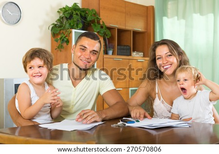 Smiling parents and two little daughters sitting at table with documents  - stock photo