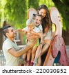 Smiling parents helping kids on slide in summer day - stock photo