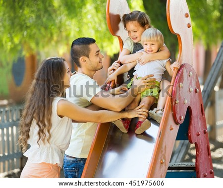 Smiling parents helping two girls  on slide in summer day  - stock photo