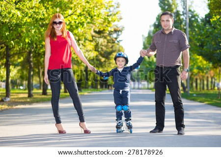 Smiling parents holding their little son riding on roller skates
