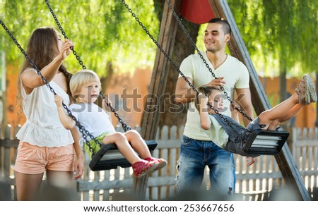 Smiling parents swinging children at park. Focus on woman - stock photo