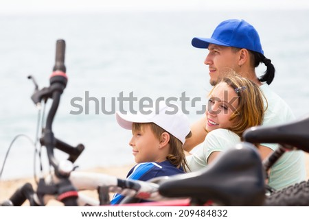 Smiling parents with teenager having rest after cycling on the beach