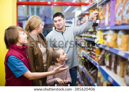 smiling parents with two kids choosing crispy flakes in shop