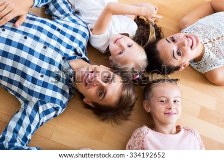 Smiling parents with two little daughters relaxing at home - stock photo