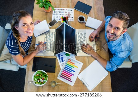 Smiling partners working at desk using laptop in the office - stock photo