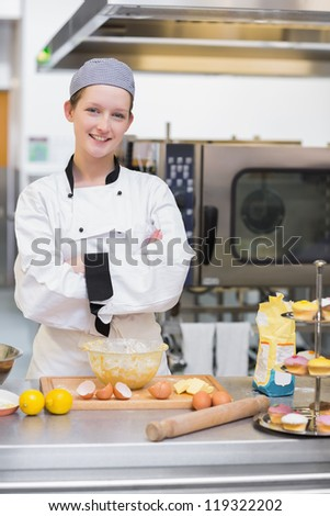 Smiling pastry chef standing behind counter in kitchen - stock photo