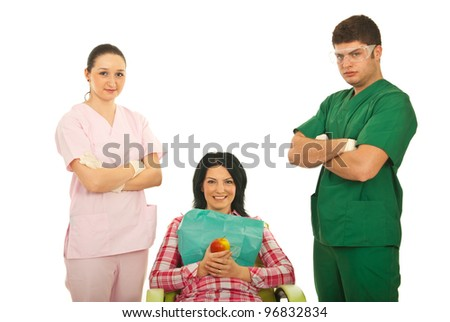 Smiling patient woman on chair holding apple in the middle of dentist team isolated on white background