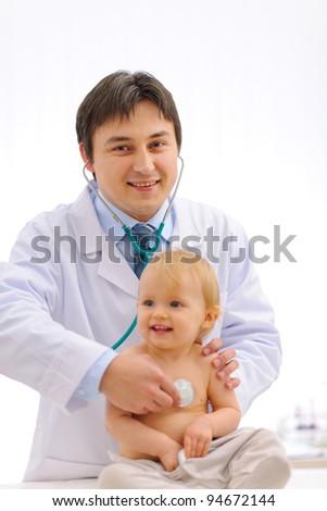 Smiling pediatric doctor checking baby using stethoscope - stock photo