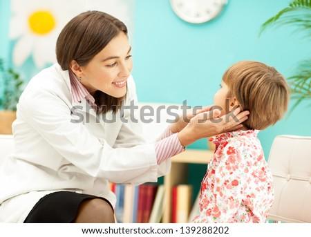 Smiling pediatrician examining a little girl. - stock photo
