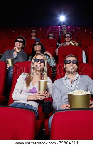 Smiling people in 3D glasses watching a movie at the cinema