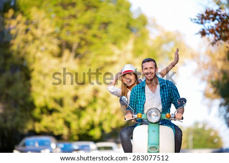 Smiling people on a scooter - stock photo