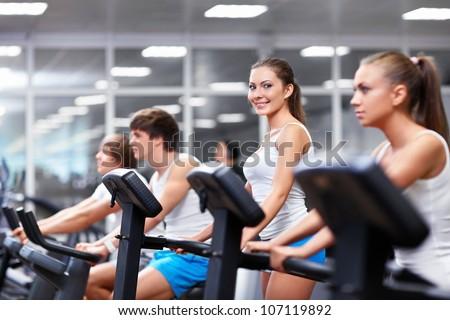 Smiling people on treadmills - stock photo