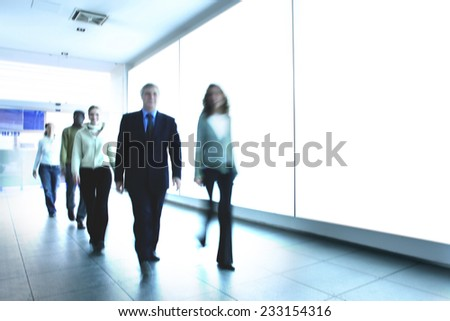 Smiling People walk in the corridor of a modern company looking forward - stock photo