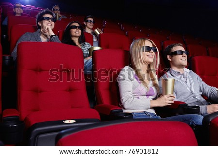 Smiling people watch movies in cinema