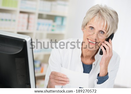 Smiling pharmacist checking up on a prescription that she is holding in her hand as she chats on the telephone to a doctor or patient - stock photo