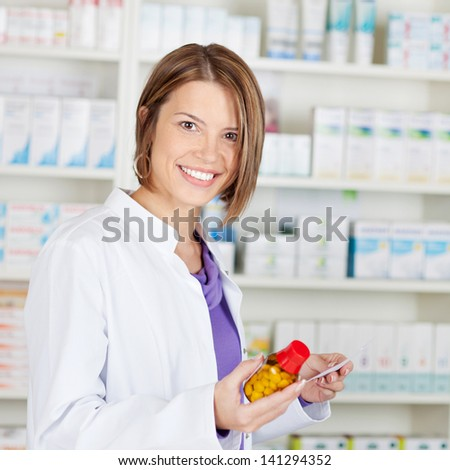 Smiling pharmacist chemist woman holding medicine in pharmacy drugstore - stock photo
