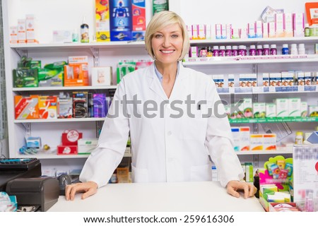Smiling pharmacist posing behind the counter in the pharmacy - stock photo