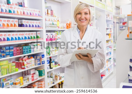 Smiling pharmacist writing on clipboard in the pharmacy - stock photo