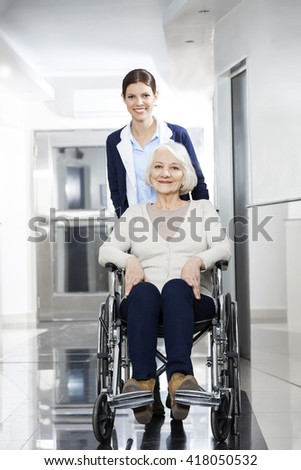 Smiling Physiotherapist Pushing Senior Woman In Wheelchair - stock photo