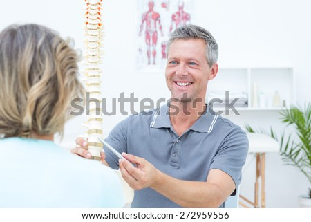 Smiling physiotherapist showing spine model to his patient in medical office - stock photo