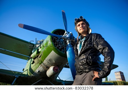 Smiling pilot in the helmet in front of vintage plane - stock photo
