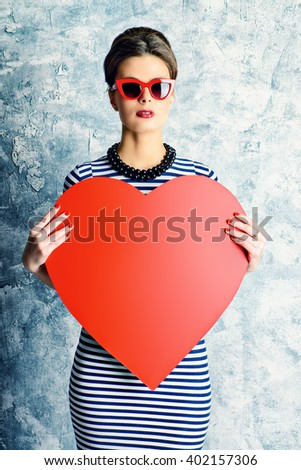 Smiling pin-up lady holding red heart. Love concept, Valentine's Day. Pin-up glasses, optics style. Beauty, fashion. - stock photo