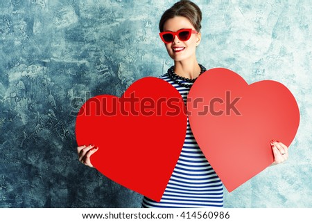 Smiling pin-up lady holding red hearts. Love concept, Valentine's Day. Pin-up glasses, optics style. Beauty, fashion. - stock photo