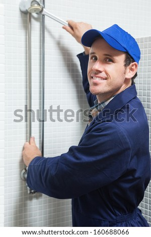 Smiling plumber repairing shower head in public bathroom - stock photo