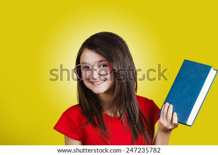 Smiling Portrait of a cute little schoolgirl loving to learn, holding with hands a book and wearing glasses isolated over yellow background.  - stock photo