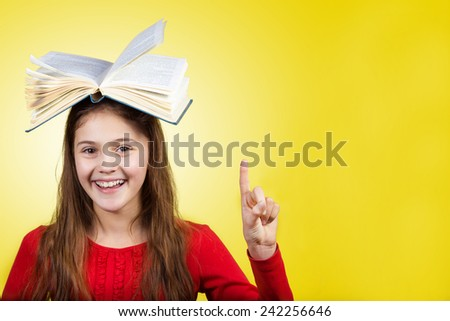 Smiling Portrait of a cute little schoolgirl loving to learn pointing up with a open book on her head, isolated over yellow background.  - stock photo