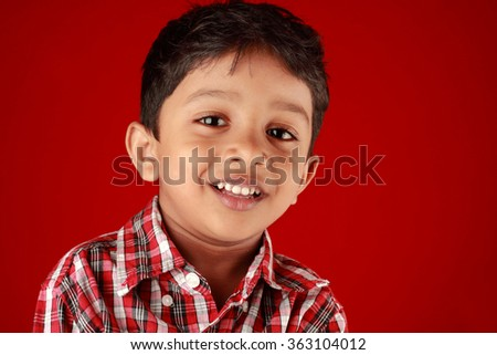 Smiling portrait of a small in a red background - stock photo