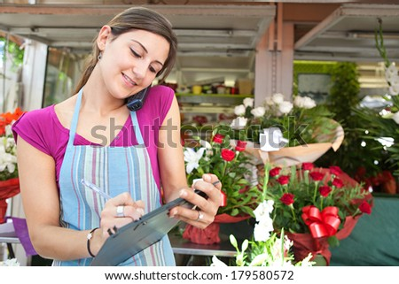 Smiling portrait of an attractive florist business woman owner at a flower shop market working and making a phone call ordering stock and running a small business, outdoors. - stock photo