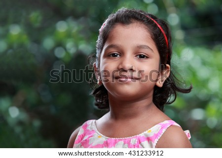 Smiling portrait of an Indian girl with outdoor background