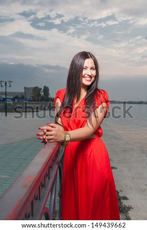 Smiling portrait of classy brunette in red shiny dress and long straight hair . Vertical shot against evening sky, outdoors. Luxury photography. - stock photo